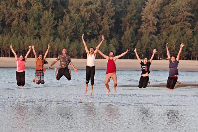 Jóvenes contentos y felices saltando en la playa